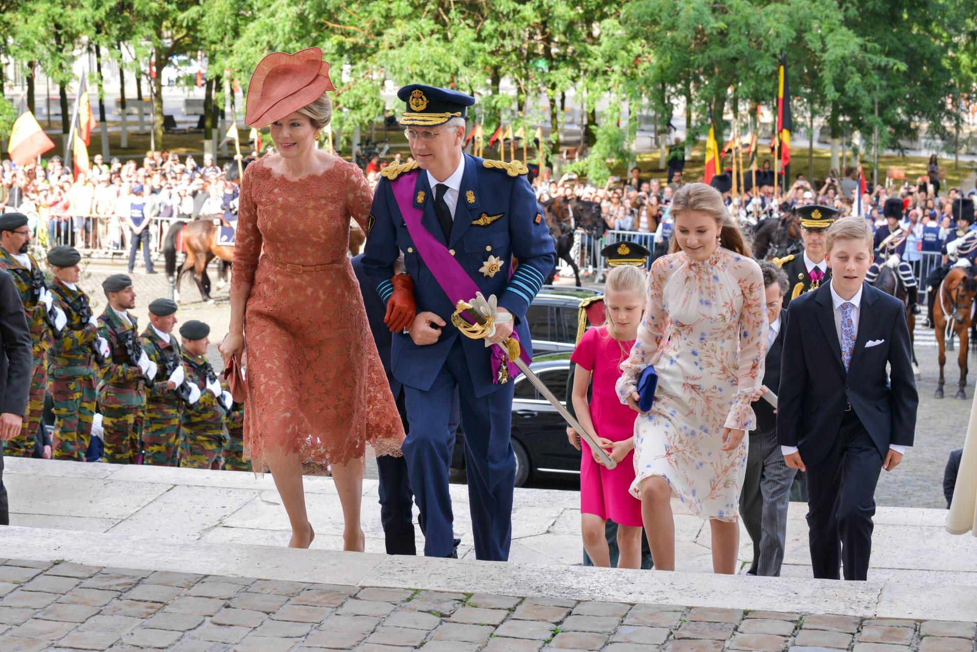 La Reine Mathilde monte les escaliers avec sa famille et porte le chapeau Birdy couleur cuivre.