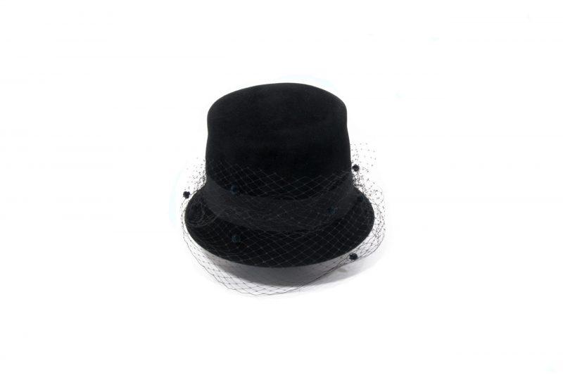 Résolument moderne, le chapeau haut-de-forme de la Maison Fabienne Delvigne est garni d'un ruban gros grain et d'une voilette mouchetée assortis.